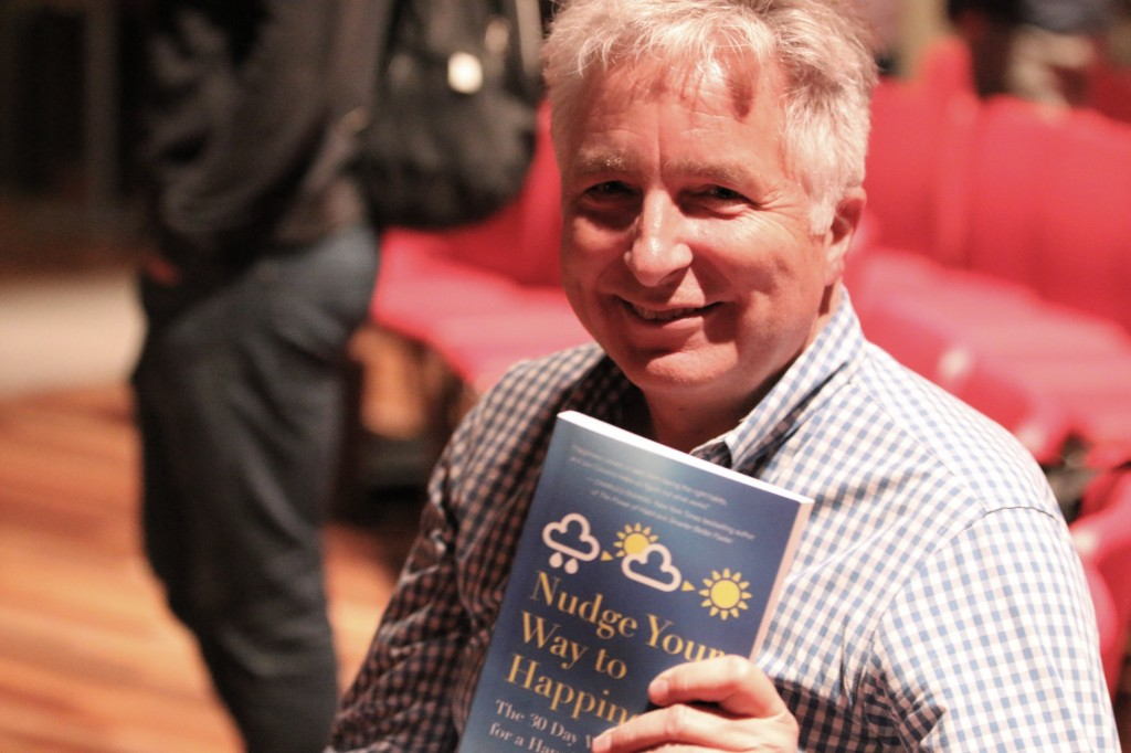 "Jon holding his book ""Nudge Your Way To Happiness"""